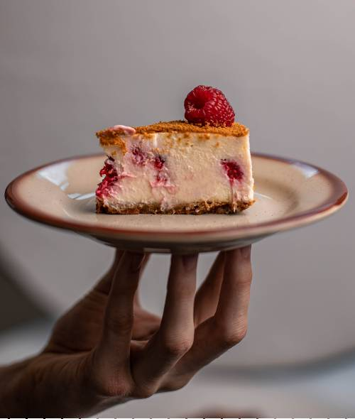 cheesecake on plate held by hand